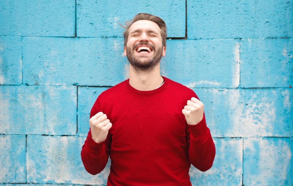 Happy man red shirt blue wall
