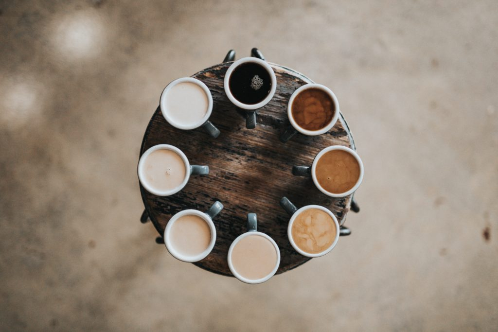 Mugs of different coloured coffee